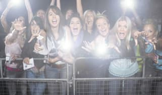 Crowd of young female fans screaming and cheering at concert