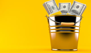 Bundles of money stick out of a bucket.