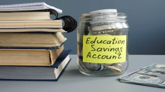 """picture of a jar with money in it labeled """"Education Savings Account"""""""