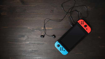 Nintendo Switch game console with blank black screen and headphones on wooden background.