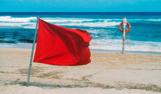 Red flag and lifebelt attached to pole on the beach. No swimming.