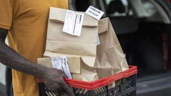 Close-up of store worker holding filled grocery bags waiting to be picked up