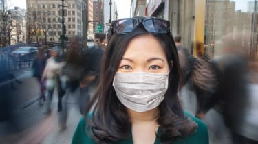 A woman wearing a mask stands on the street in New York City.