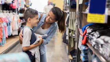 Happy young boy looks at a shirt in the mirror while shopping for back to school clothes with his mom.
