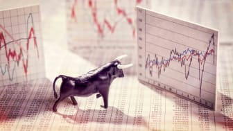 Bull toy looking at market charts