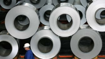 SZEKESFEHERVAR, HUNGARY - OCTOBER 24:A worker walks among rolls of semi-finished aluminum at the Alcoa aluminum factory October 24, 2006 in Szekesefehervar, Hungary. Alcoa bought the factory,
