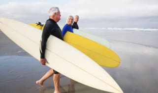 Three men walk toward the water with surfboards.