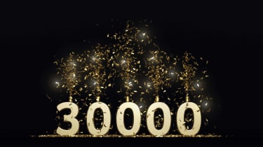The number 30,000, but with sparkler candles coming out of the tops of each number