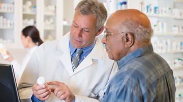 Pharmacist explains prescription to senior man