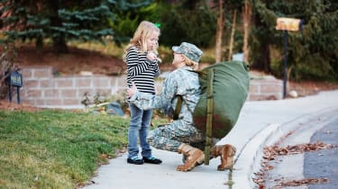 Military mother in uniform saying goodbye other daughter.