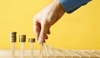 concept image of investing and banking. A businessman stops the domino effect from risking financial investment