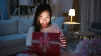 A young woman opens a red gift box