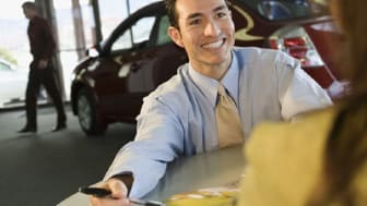 Car salesman smiling at customer