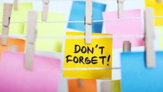 "adhesive note paper with ""don't forget!"" text hanging on the rope"