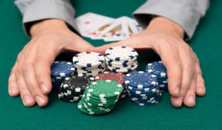 picture of person grabbing a pile of poker chips after winning a hand