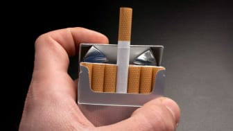 A man opening a pack of cigarettes