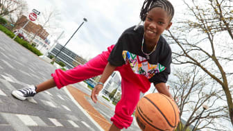 A child bounces a basketball on a court while wearing Justice apparel