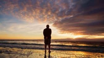 A man stands on a beach at sunset.