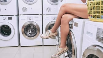 Beautiful legs of woman sitting on washing machine in laundry room