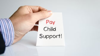 """picture of man's hand hold a note saying """"pay child support"""""""