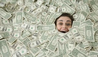 picture of a woman's face sticking out from a pile of money