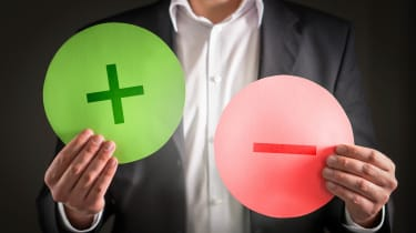 A man holds up a green plus sign and a red minus sign.
