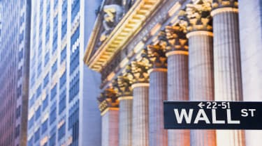 picture of Wall Street sign with New York Stock Exchange in the background