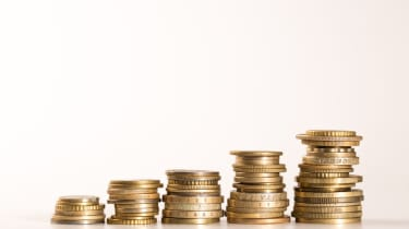Five stacks of golden coins growing on white background