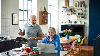 Senior couple in kitchen on laptop