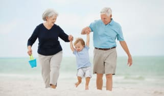 Grandparents playing with a grandson on a beach.