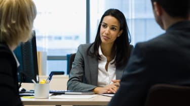 A financial adviser meets with two clients.