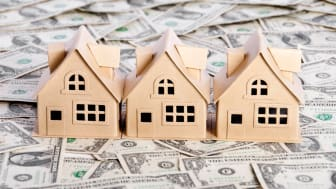 picture of small model housing on a table covered with money