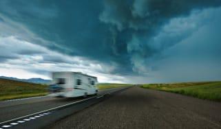 A motor home drives toward a storm.