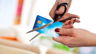 woman cuts credit card with scissors