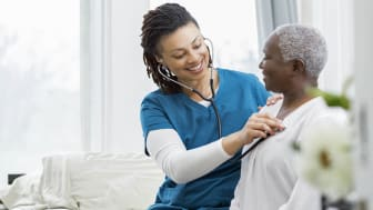 Young African American home healthcare nurse checks a senior female patient's vital signs. The senior woman is recovering at home from a recent surgery.