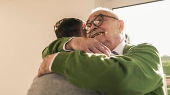 A retiree hugs a friend.