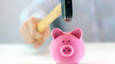 picture of man about to break piggy bank with a hammer