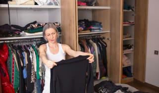 Senior woman sorting through her clothes in her closet while decluttering