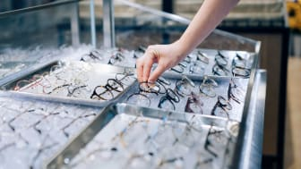 Cropped shot of a woman selecting eyeglasses from retail display in optical shop