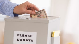 picture of person putting money in a donation collection box