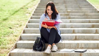 College kid sitting on steps with a book smiling