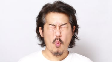 A man puckers up his face as if tasting something sour.
