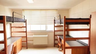 An empty university dormitory room with desk bed and closet.