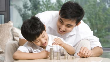 Photo of a boy and his father stacking coins