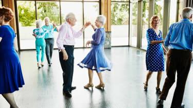 An elderly man twirls his partner on the dance floor.