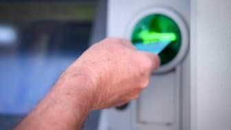 A person puts their bank card into an ATM.
