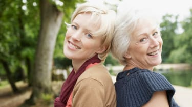 A senior mom and her adult daughter smile together.