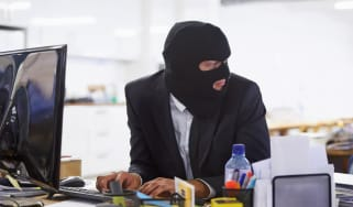 Shot of a hacker dressed in a black mask hacking a computerhttp://195.154.178.81/DATA/i_collage/pi/shoots/783303.jpg