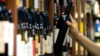 A bottle of wine being removed from a shelf of wines