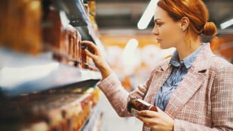Woman looking at canned-jarred items on a supermarket food shelf.